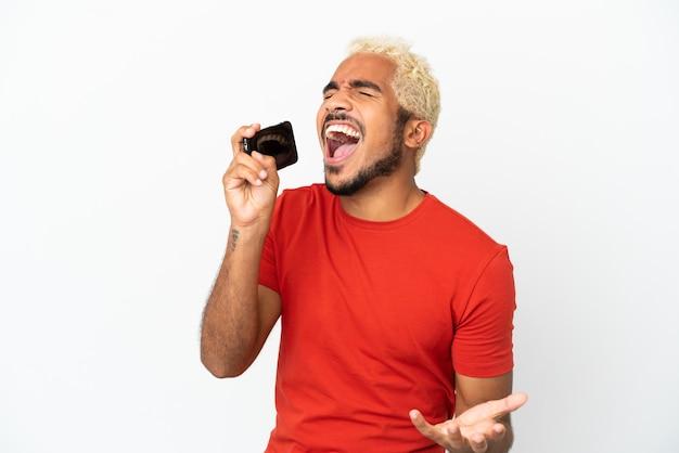 Jeune bel homme colombien isolé sur fond blanc utilisant un téléphone portable et chantant