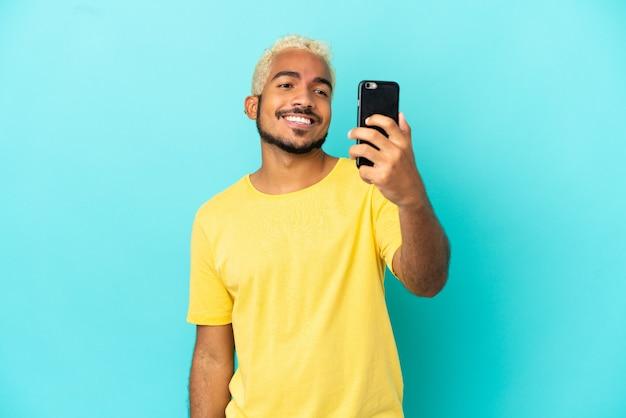 Jeune bel homme colombien isolé sur fond bleu faisant un selfie
