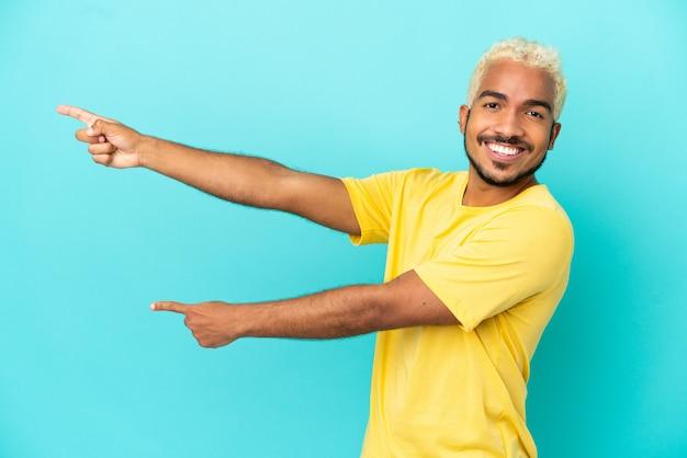 Jeune bel homme colombien isolé sur fond bleu, pointant le doigt sur le côté et présentant un produit