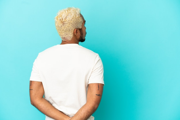 Jeune bel homme colombien isolé sur fond bleu en position arrière et regardant en arrière