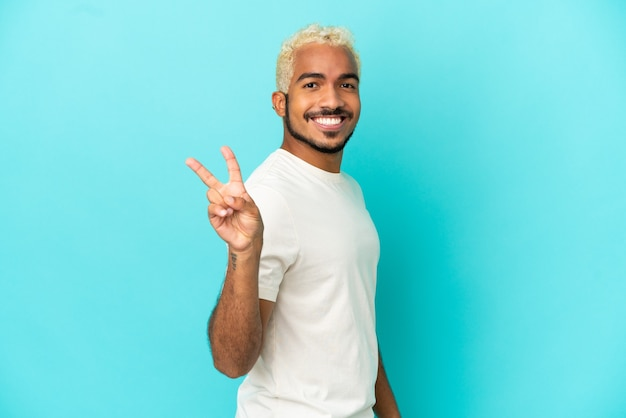 Jeune bel homme colombien isolé sur fond bleu souriant et montrant le signe de la victoire