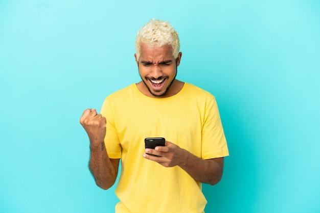 Jeune bel homme colombien isolé sur fond bleu surpris et envoyant un message