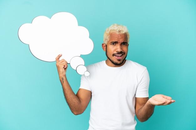 Jeune bel homme colombien isolé sur fond bleu tenant une bulle de pensée et avec une expression triste