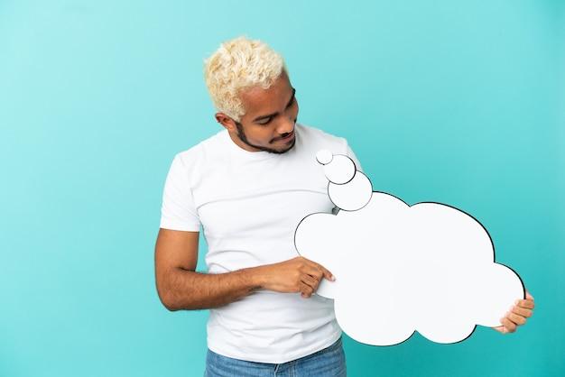 Jeune bel homme colombien isolé sur fond bleu tenant une bulle de pensée