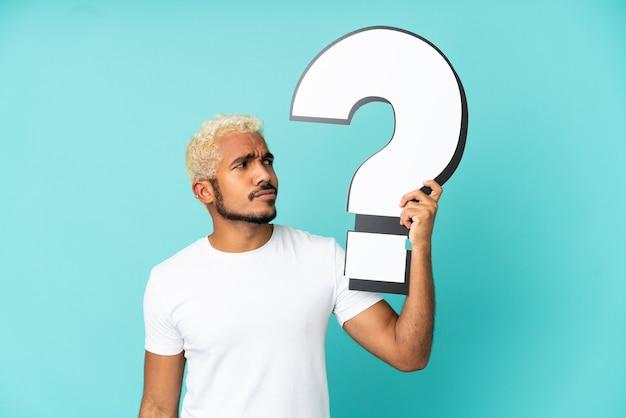Jeune bel homme colombien isolé sur fond bleu tenant une icône de point d'interrogation et ayant des doutes
