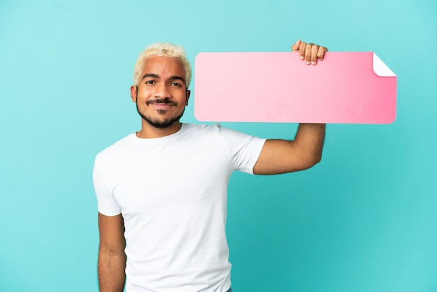 Jeune bel homme colombien isolé sur fond bleu tenant une pancarte vide