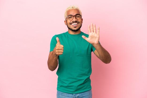 Jeune bel homme colombien isolé sur fond rose comptant six avec les doigts