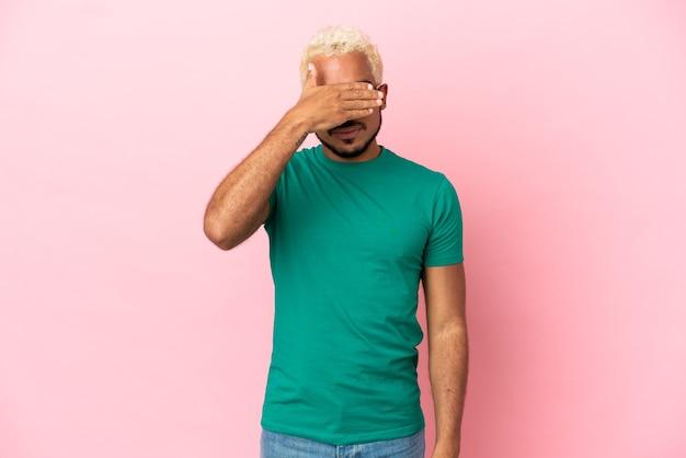Jeune bel homme colombien isolé sur fond rose couvrant les yeux par les mains. je ne veux pas voir quelque chose