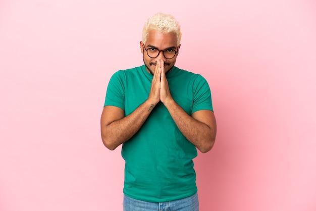 Jeune bel homme colombien isolé sur fond rose maintient la paume ensemble. la personne demande quelque chose