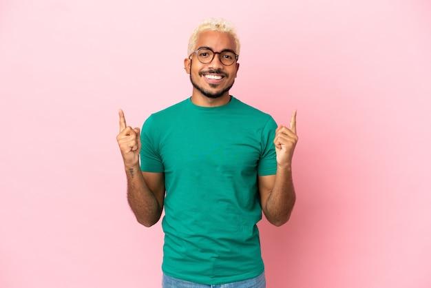 Jeune bel homme colombien isolé sur fond rose pointant vers une excellente idée