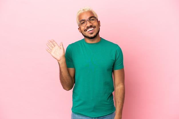 Jeune bel homme colombien isolé sur fond rose saluant avec la main avec une expression heureuse