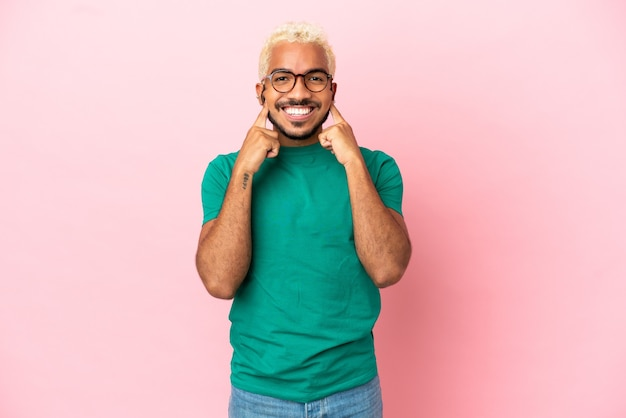 Jeune bel homme colombien isolé sur fond rose souriant avec une expression heureuse et agréable