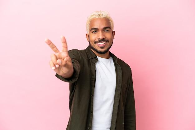 Jeune bel homme colombien isolé sur fond rose souriant et montrant le signe de la victoire