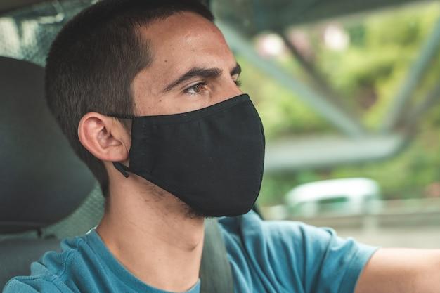Jeune bel homme conduisant une voiture avec un masque chirurgical pour prévenir le concept de coronavirus pandémique
