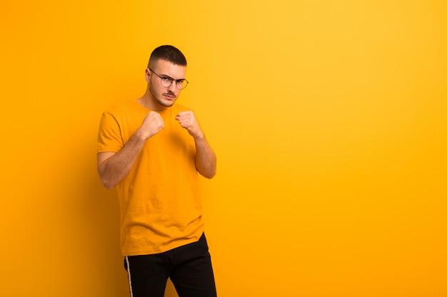 Jeune bel homme à la confiance, en colère, fort et agressif, avec les poings prêts à se battre en position de boxe contre un mur plat