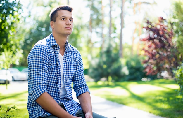 Jeune bel homme confiant dans une chemise à carreaux alors qu'il repose sur le banc à l'extérieur