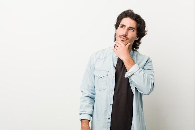 Jeune bel homme contre un mur blanc à côté avec une expression douteuse et sceptique.