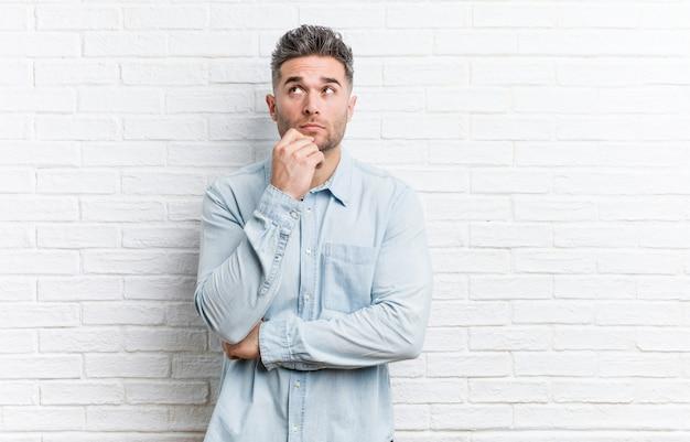Jeune bel homme contre un mur de briques, regardant de côté avec une expression douteuse et sceptique.