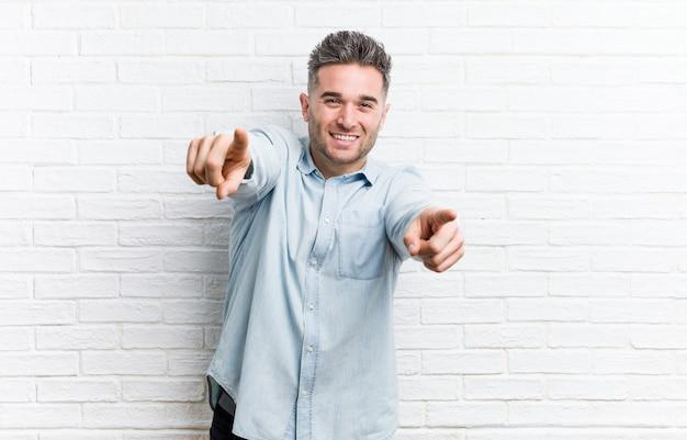Jeune bel homme contre un mur de briques sourires joyeux pointant vers l'avant.