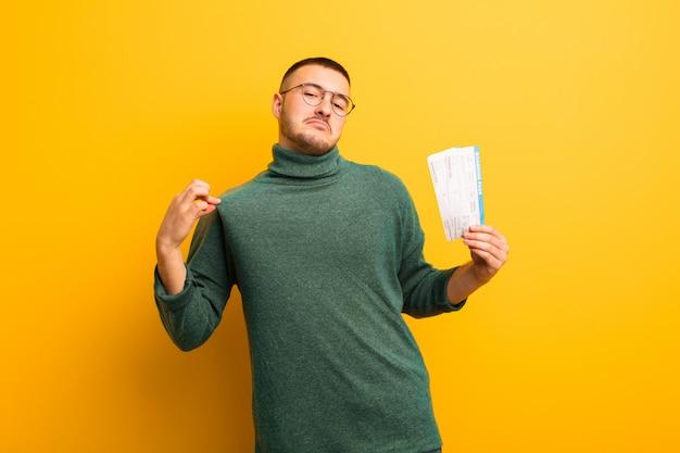 Jeune bel homme contre un mur plat avec des billets de carte d'embarquement
