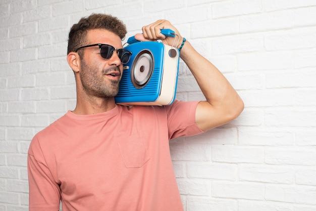 Jeune bel homme cool écoute de la musique avec une radio vintage