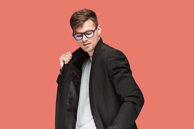 Jeune bel homme en costume noir et lunettes isolés sur l'espace rouge