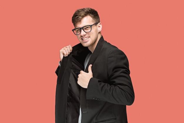 Jeune bel homme en costume noir et lunettes isolés sur rouge