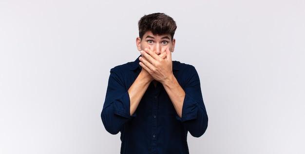 Jeune bel homme couvrant la bouche avec les mains avec une expression choquée et surprise, gardant un secret ou disant oups