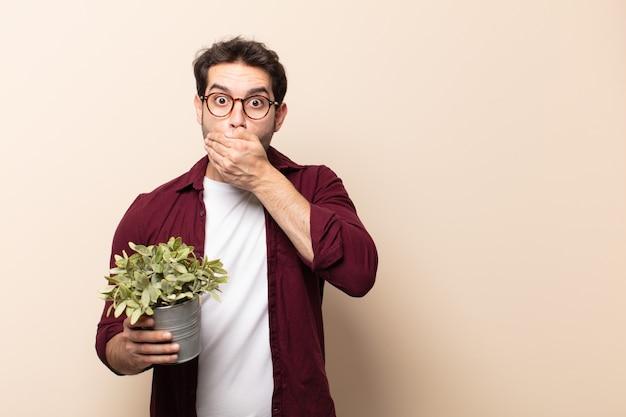 Jeune bel homme couvrant la bouche avec les mains avec une expression choquée et surprise, en gardant un secret ou en disant oups