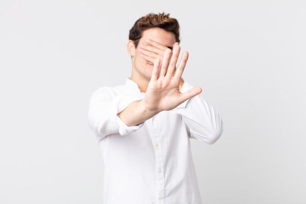 Jeune bel homme couvrant le visage avec la main et mettant l'autre main devant pour arrêter l'appareil photo, refusant des photos ou des images