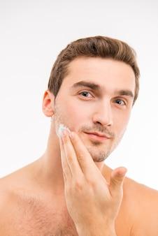 Un jeune bel homme avec de la crème à raser sur sa joue