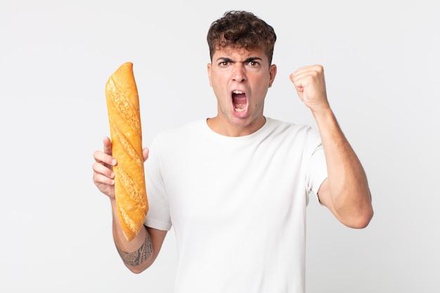 Jeune bel homme criant agressivement avec une expression de colère et tenant une baguette de pain