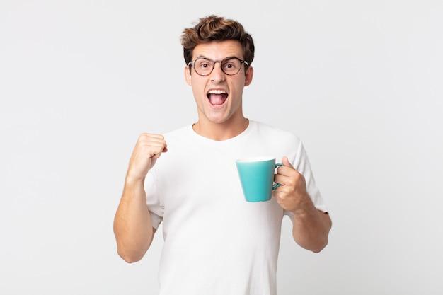 Jeune bel homme criant agressivement avec une expression de colère et tenant une tasse de café
