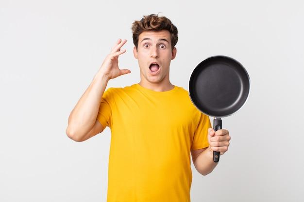 Jeune bel homme criant avec les mains en l'air et tenant une casserole