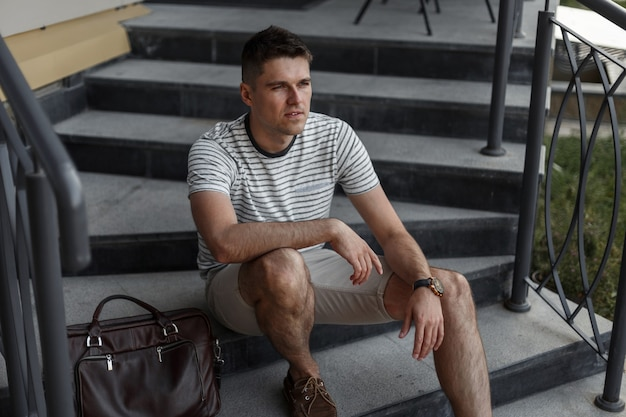 Jeune bel homme dans un élégant t-shirt rayé d'été en short à la mode en chaussures en daim avec un sac en cuir se trouve sur un escalier en pierre