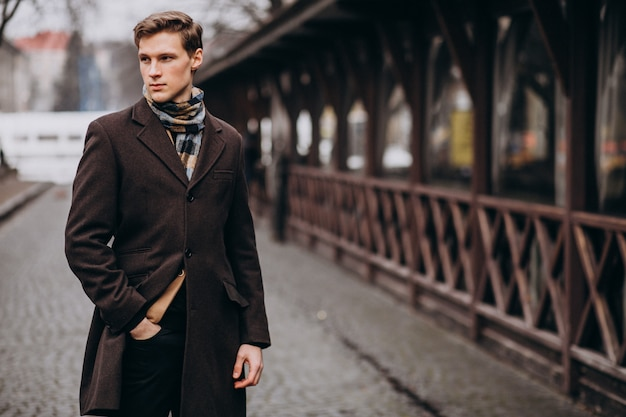 Jeune bel homme dans un manteau à l'extérieur de la rue