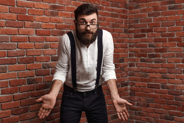 Jeune bel homme dans des verres, gesticulant sur le mur de briques.