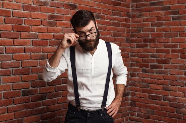 Jeune bel homme dans des verres sur le mur de briques.