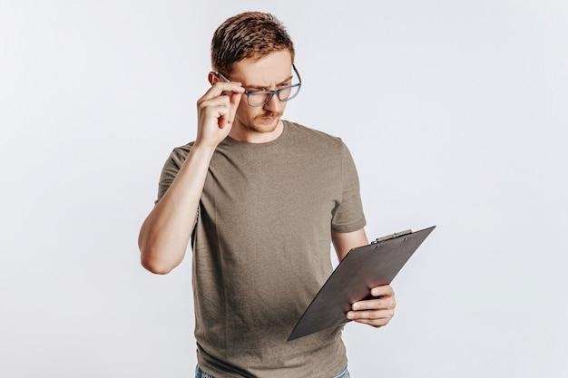Jeune bel homme dans des verres tenant le dossier pour les papiers avec des documents