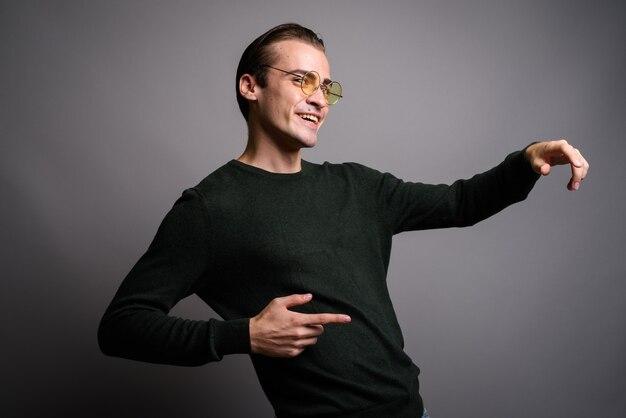 Jeune bel homme dansant sur studio gris