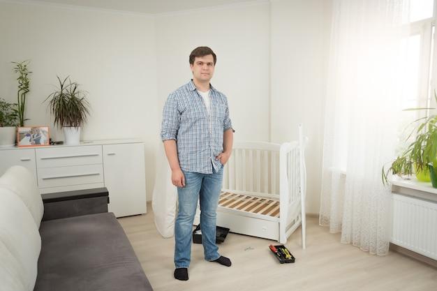 Jeune bel homme debout au lit bébé démonté dans la chambre