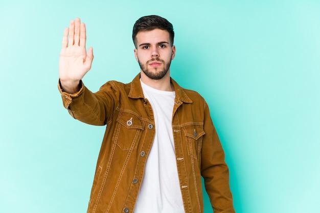 Jeune bel homme debout avec la main tendue montrant le panneau d'arrêt, vous empêchant.