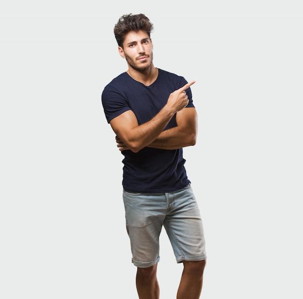 Jeune bel homme debout pointant sur le côté, souriant surpris de présenter quelque chose, naturel et désinvolte