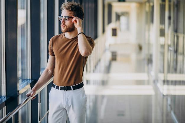 Jeune bel homme debout près de la fenêtre à l'aéroport