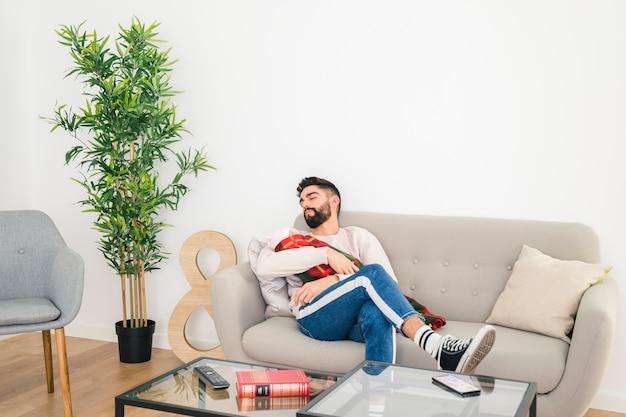 Jeune bel homme dort sur le canapé avec son bébé dans la main à la maison