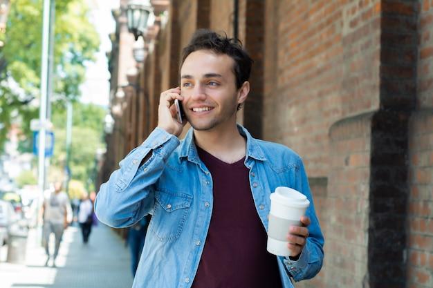 Jeune bel homme avec du café jetable