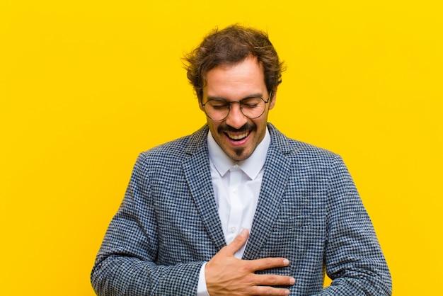 Jeune bel homme éclater de rire à la suite d'une blague hilarante, se sentir heureux et gai, s'amuser contre le mur orange