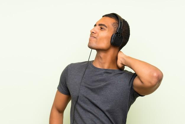 Jeune bel homme écoute de la musique avec un téléphone portable sur un mur vert isolé