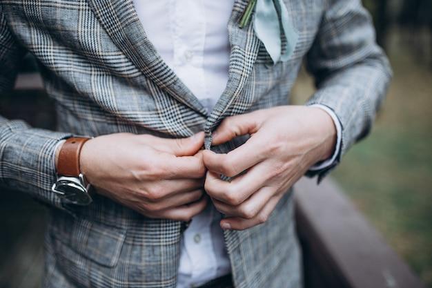 Jeune bel homme élégant habillé en veste de boutonnage de vêtements formels modernes. gros plan des mains de gars en veste grise, chemise violette. personne prête pour la célébration du mariage ou l'obtention du diplôme.