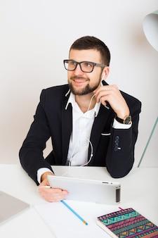 Jeune bel homme élégant hipster en veste noire travaillant à la table de bureau, style d'affaires, chemise blanche, isolé, ordinateur portable, démarrage, lieu de travail, crayon, feuilles de papier, occupé